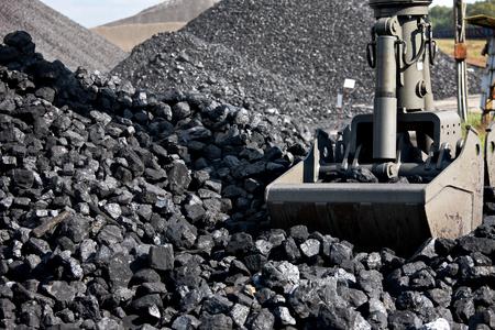 Coal loading excavator, heaps of coal