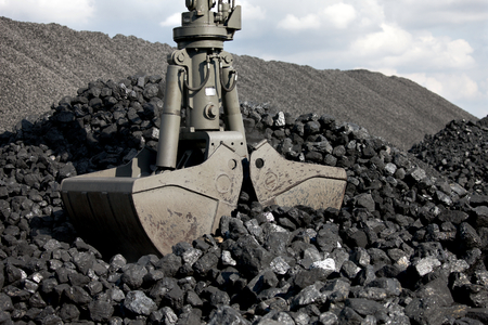Coal loading excavator, heaps of coal