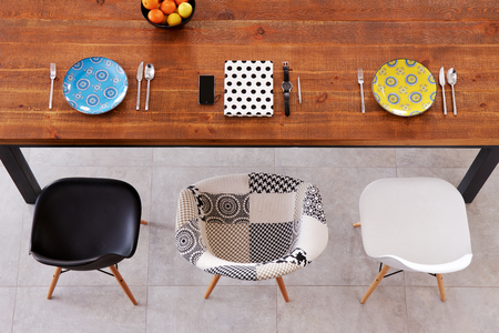 dining table and chairs: Dining wooden table, color porcelain plates, phone, watch and notebook
