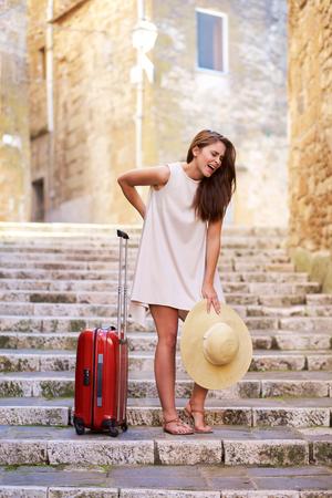 femme valise: Jeune femme souffre de douleurs au dos en soulevant une lourde valise Banque d'images