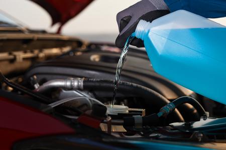 男が彼の車の不凍液を充填