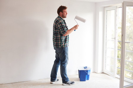 Young man painting a wall on a white color background in a modern home Archivio Fotografico