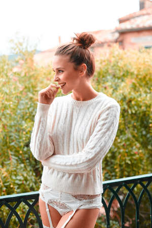 Pretty laughing beautiful young woman in white sweater and underwear, standing on balcony. Tuscany, Italy. Small depth of field.