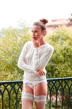 Beautiful young and pensive woman in white sweater and underwear, standing on balcony. Tuscany, Italy. Small depth of field.