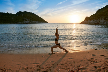 Silhouette yoga practice at sunset. Young woman doing yoga exercise on the beautiful beach. Corfu, Greece.