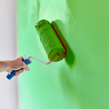 Male hand painting wall with paint roller. Painting apartment, renovating with green color paint Stockfoto
