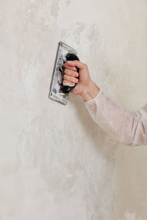 Hand of a man sanding a wall after plastering Banque d'images - 136103553