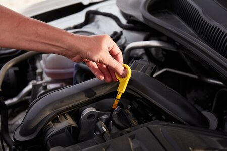 Checking engine oil. A woman's hand holding an oil bayonet in a modern popular car. The concept of the engine problem.