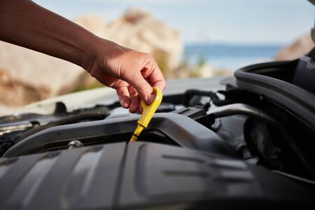 Checking engine oil. A womans hand holding an oil bayonet in a modern popular car. Stockfoto