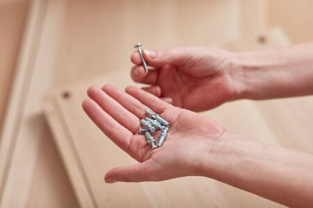 Female hands holding the screws in their hands. Concept for self-contained, easy furniture assembly. Banque d'images