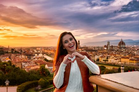 A young woman holding her hands in a gesture of heart with the panorama of Florence behind it at sunset.