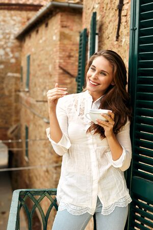 Portrait of happy young woman on vacation, standing on the balcony of an old building in a Tuscan town.