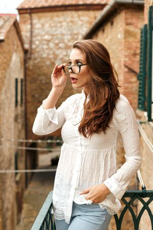 Portrait of the surprised young woman on vacation, standing on the balcony of an old building in a Tuscan town. Stockfoto