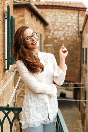A portrait of a young woman laughing, standing on the balcony of a typical old house in a Tuscan town