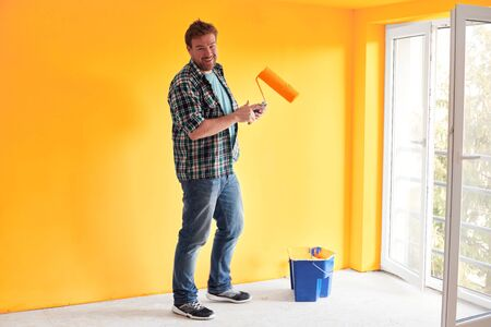 Young man painting a wall on sunflower color in a modern home