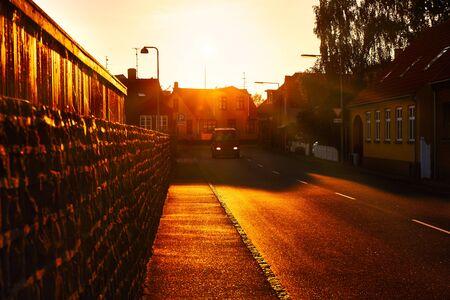 A van driving through town at sunset Stockfoto
