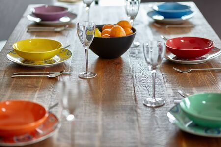Wooden table with colourful dinnerware Small depth of field.