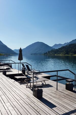 Hotel terrace with deck chairs on the shores of an alpine lake surrounded by mountains