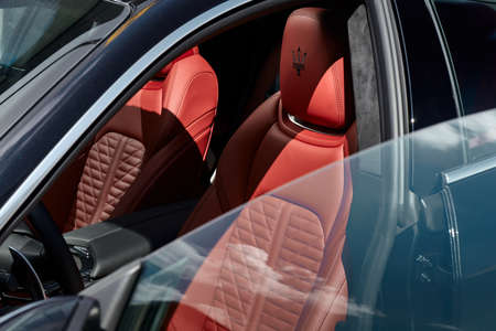 Warsaw / Poland - 08.01.2018 : Maserati Ghibli interior with red leather seats, seen through open doors with frameless windows.