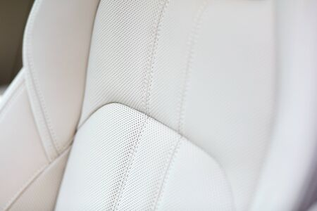 White leather seat of an expensive and luxurious car. Shallow depth of field.
