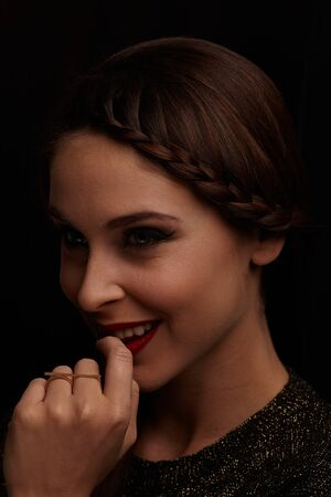 A portrait of a beautiful and cheerful woman in the dark. Lighting in Rembrandt style. Stockfoto