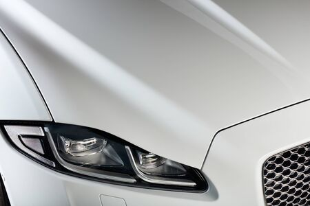 The headlight and bonnet of a white car. A modern and luxurious car.