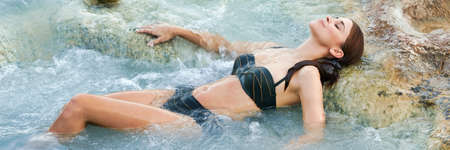 Pretty young brunette woman taking a bath in the natural geothermal waters of spa. Saturnia, Italy Standard-Bild