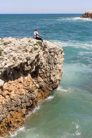 fishman: fisherman at the cliff border , Cantabria, Spain Stock Photo