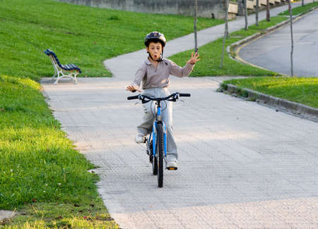 a boy is riding bike without hands photo