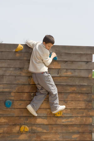 exercice: child climbing  a wooden wall at the park Stock Photo