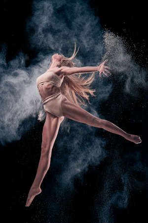 Slim woman dancing with sand. black studio