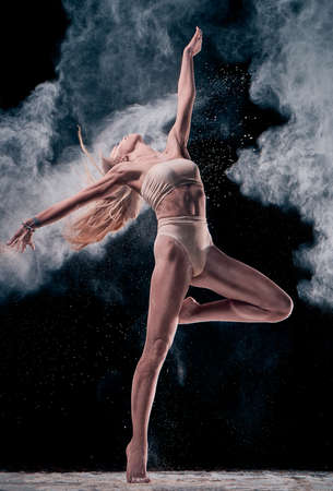 The dance of the body, girl performing with cloud of flour, black background