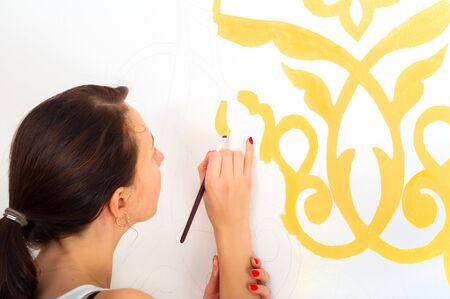 decorating: Beautiful girl decorating wall
