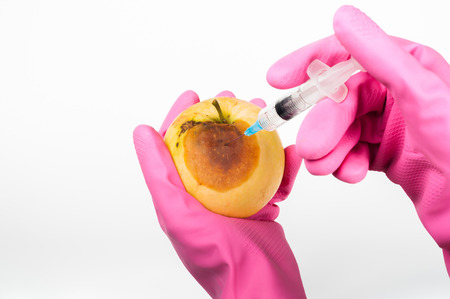 modified: Genetically modified apple with syringe Stock Photo