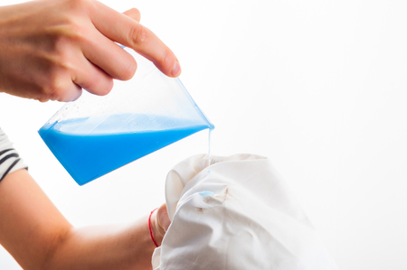Removing stain from white shirt measuring determent by hand
