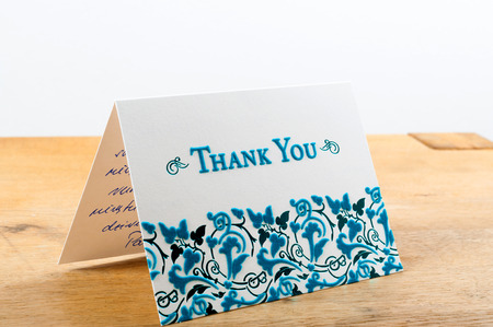 White thank you card with blue letters with note written by hand Stock Photo