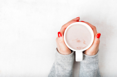 Woman with red fingernaild holding cup of hot cacao beverage on white wooden background