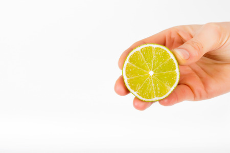 Holding lime in hand. White clean background. Fruit in hand Stock Photo