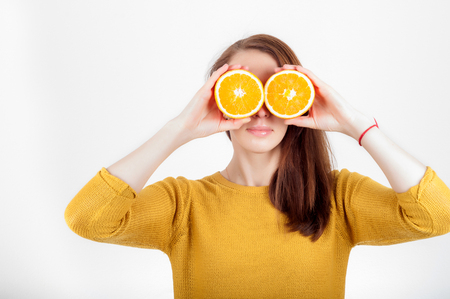 see through: Healthy eating concept. Joyful happy young woman holding juicy oranges before her eyes. Isolated over white.