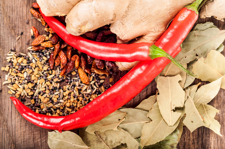 Seasoning concept - Assortment of fresh and dry spices on wooden background, chili, bay leaves, ginger, coriander, seeds