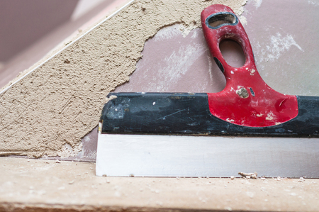 plasterer: Repairing fireplace surface with spackle and trowel by hand