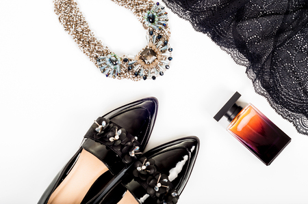 Feminine classic fashion concept. Black patent leather shoes with lace dress, perfume and jewelry on white background. Top view Stock Photo