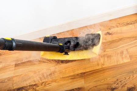 寄木細工の床、木製ラミネートの床の部屋で蒸気で洗浄します。レギュラーをクリーンアップします。クリーニングの概念