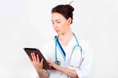 Portrait of young attractive doctor, surgeon, nurse with stethoscope and tablet Stock Photo