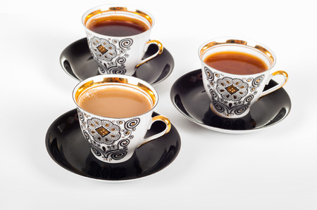 choise: Three cups of coffee with black, white and flowing milk on white background