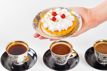 Womans hand holding small cake on beautiful set plate