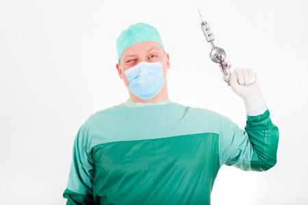 Cirujano que sostiene el taladro médico antiguo, pasado de moda en el fondo blanco