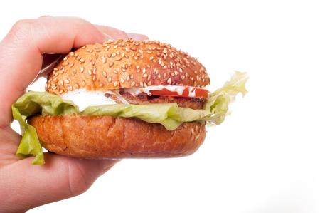 Hand holds fresh hamburger. Isolated on a white background Stock Photo