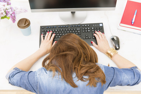 Young pretty woman tired and exhausted of work lying on table in front of computer and taking a break