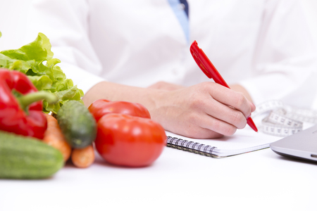 dietetics: Vegetable diet nutrition or medicaments concept. Doctors hands writing diet plan, ripe vegetable composition, laptop and measuring tape on white background